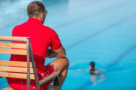 Lifeguard in chair, overlooking swimming pool Stock Photo