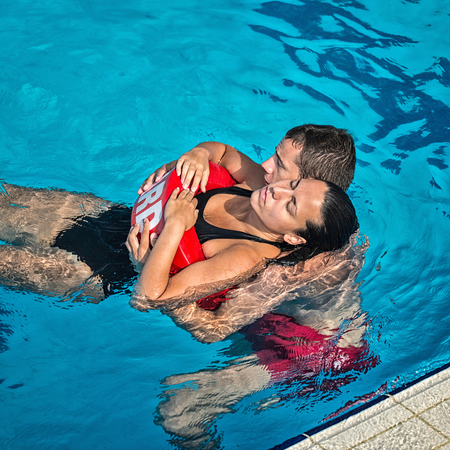 rescuing: Lifeguard rescuing victim from swimming pool Stock Photo