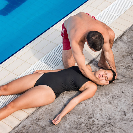 recovery position: Lifeguard placing accident victim in recovery position Stock Photo