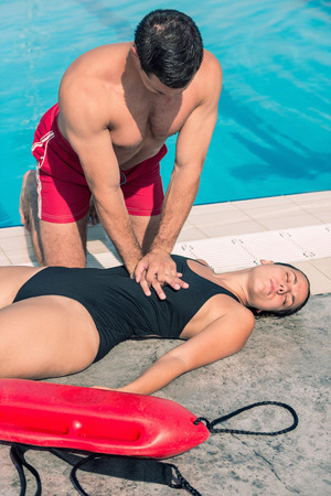 recovery position: Lifeguard doing CPR after swimming pool accident. Toned image Stock Photo