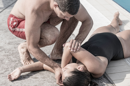 recovery position: Lifeguard positioning swimming pool accident victim