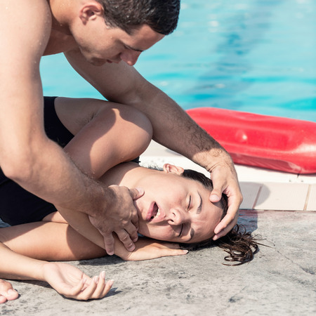 recovery position: Lifeguard performing medical procedure with swimming pool accident victim