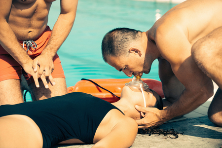 chest compression: Lifeguard training - CPR Procedure. Toned image Stock Photo
