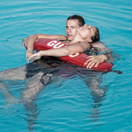 Lifeguard rescuing victim from water Stock Photo