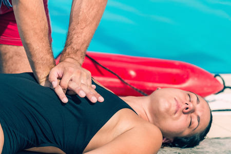 recovery position: Lifeguard doing CPR exercise by the pool