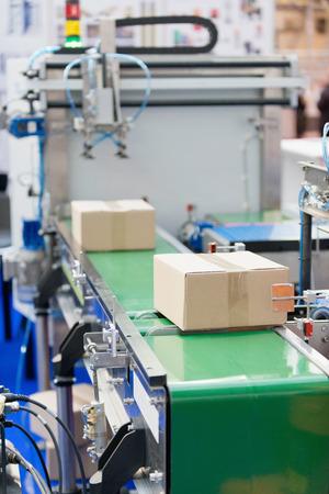 conveyor belt: Industrial packaging machine, boxes moving on conveyor belt
