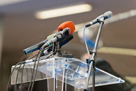 Microphones waiting on a press conference stand Stock Photo