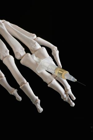 skeleton hand: Drug abuse dangers - skeleton hand holding syringe with substance