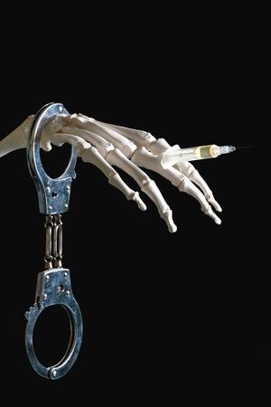 decease: Drug addiction - conceptual image with handcuffed skeleton hand holding syringe with substance, shot on black background