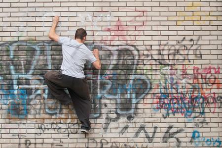 Junger Mann mit einem Grafitti Mauer klettern