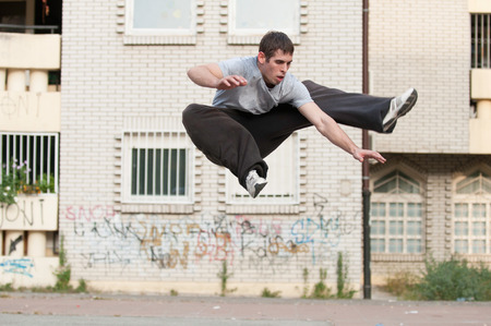 Parkour runner caught in mid air. Selective focus set on model with blurred urban background, no motion blur.