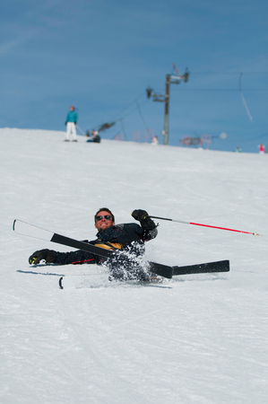 polarization: Skier falling down with a smile on a sunny ski slope. Selective focus, polarization filter Stock Photo