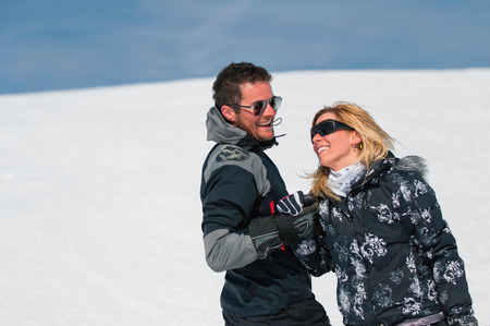 ski couple holding hands and smiling on a snowy mountain