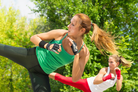 female boxing: Two young women demonstrating side kicks in taebo training