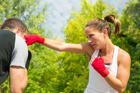 two persons only: Instructor avoiding punches in TaeBo training. Focus on girl, hand in motion blur
