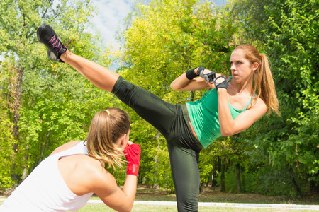 two persons only: Young woman doing side kick with another in guard stance