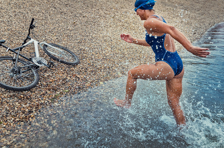 triathlete: Triathlete in training - running towards bicycle after swimming