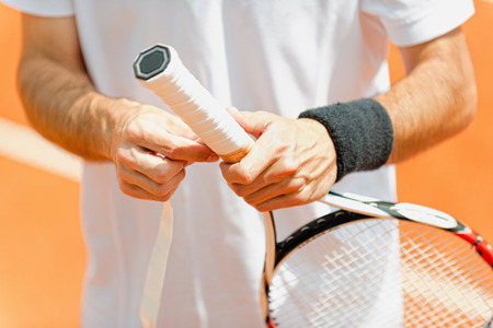 grip: Tennis professional putting new grip tape on tennis racket