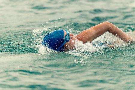 swimming cap: Triathlon training - athlete swimming