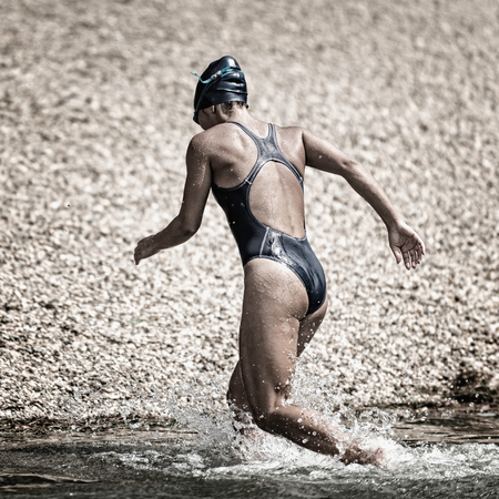 toned image: Triathlete coming out of water. Toned image Stock Photo