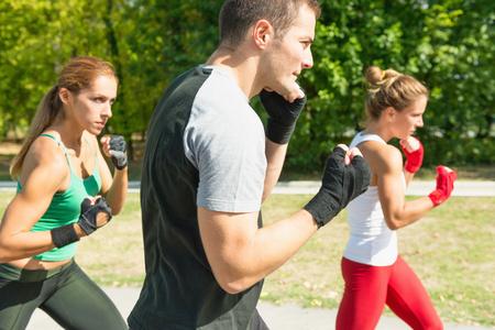 three persons only: Taebo team in training, doing uppercut punch