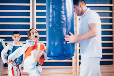 Child kicking punching bag on tae kwon do class