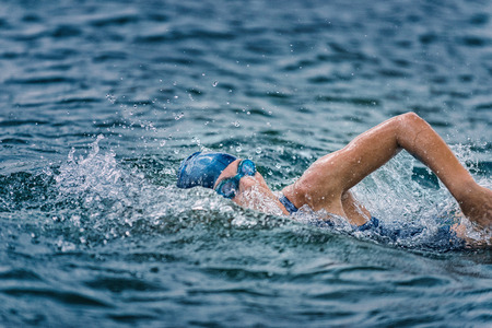 swimming goggles: Open water swimming - female athlete swimming long distance