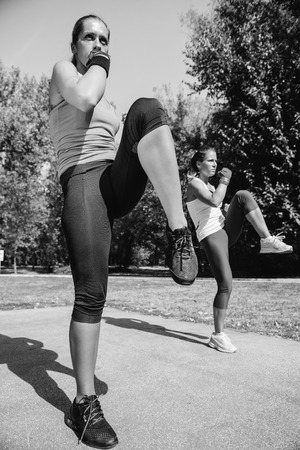 two persons only: Females doing front kicks on taebo training