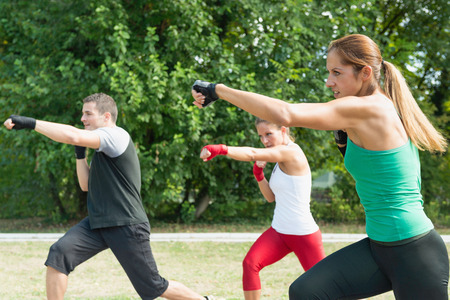 three persons only: Three people on tae bo training in park