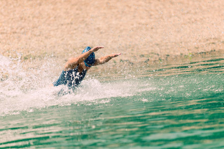 triathlete: Triathlete in training, running into a lake Stock Photo