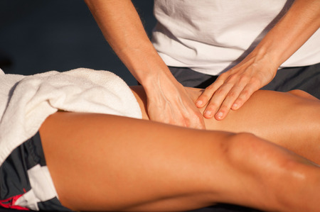 Sport therapist massaging of leg of an athlete