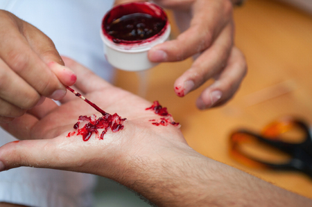 special effects: Special effects make up artist creating a hand injury. Selective focus set on the wound