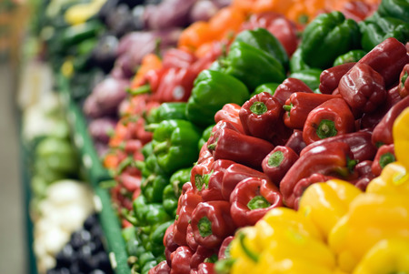 greem: Heaps of peppers in the market stall. Strong depth of field, focus set on red peppers