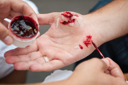 special effects: Special effects make up artist creating realistic hand injuries Stock Photo