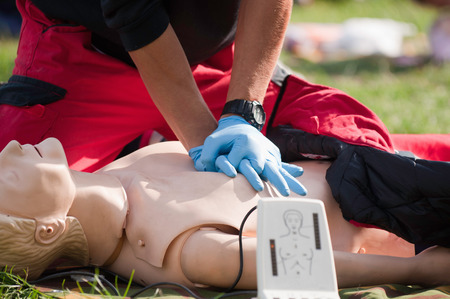 Practicing chest compressions on a CPR dummy Stock Photo