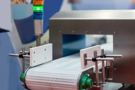 Metalldetektor-Förderbandmaschine - wird verwendet, um die Qualität von Lebensmitteln oder anderen Produkten zu kontrollieren. Der Alarm wird ausgelöst, wenn das System ein fehlerhaftes oder verunreinigtes Produkt erkennt. Standard-Bild