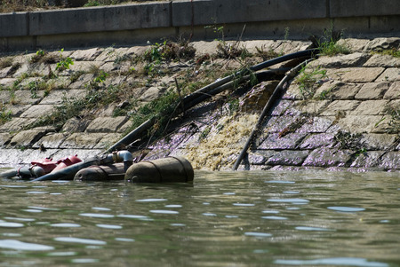 polluting: Sewage outlet polluting the river