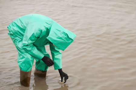 protective suit: Environment inspector in protective suit sampling polluted water. Selective focus set on the flask.