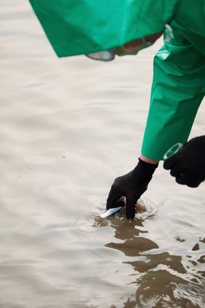 protective suit: Man in protective suit sampling polluted water Stock Photo