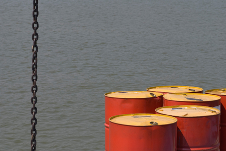 toxic substance: Water pollution concept - oil barrels against the water. Selective focus set on barrels, convenient copy space.