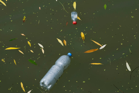 polluting: Water pollution: plastic bottles polluting the river
