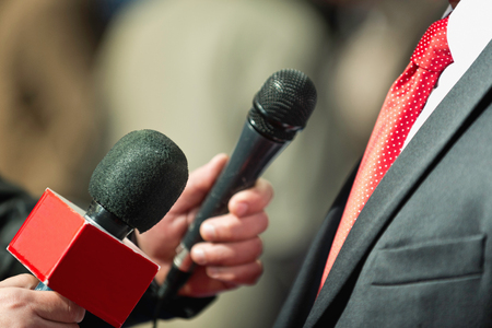 spokesman: Media Interview - journalists with microphones interviewing formal dressed person Stock Photo