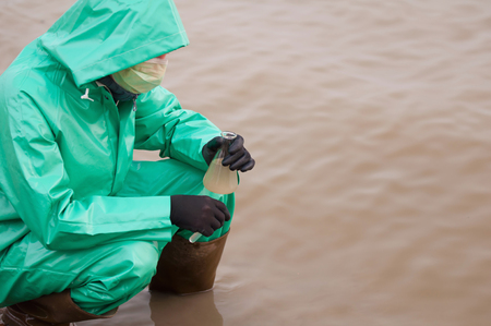 environmentalist: Environmentalist in protective suit holding a flask with sample of dirty water