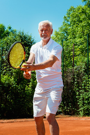 70s tennis: Senior tennis player serving Stock Photo