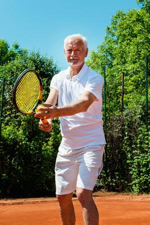 70s tennis: Senior tennis player serving Stock Photo