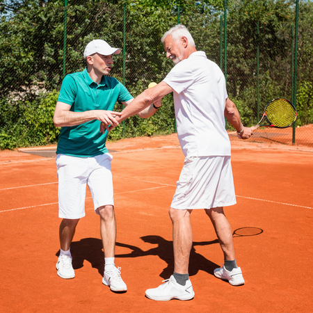 70s tennis: Tennis instructor working with senior man, practicing position for forehand stroke