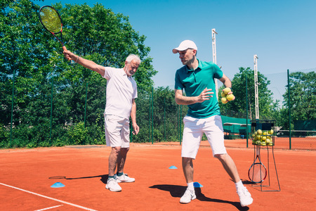 70s tennis: Senior man having tennis lesson with instructor, toned image Stock Photo