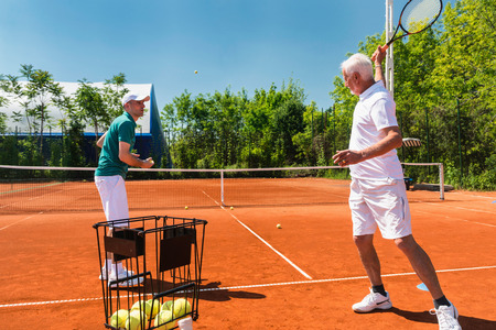 70s tennis: Active senior on tennis class with instructor Stock Photo
