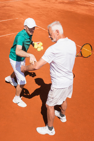 70s tennis: Senior man learning tennis with instructor