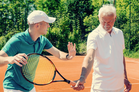 70s tennis: Tennis class for seniors, elderly man working with tennis instructor. Toned image